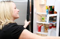 woman looking at food in fridge